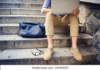 Detail of modern hipster man�´s feet sitting on the stairs and using laptop