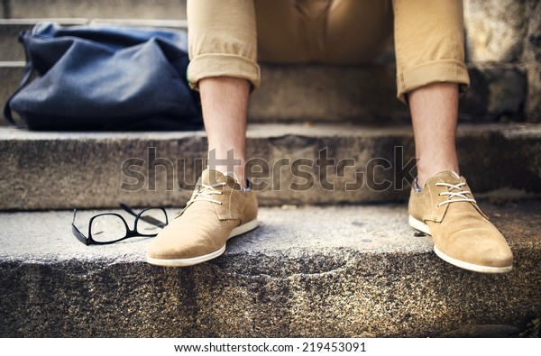 Detail of modern hipster man�´s feet sitting on the stairs