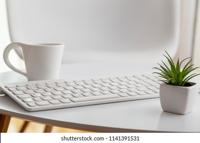 Detail of a modern home interior; white minimalistic home office atmosphere. Selective focus on the keyboard