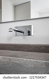 detail of a modern steel faucet in the bathroom