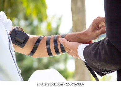 Detail of the moment when the Jewish rabbi puts the tefillin on the bridegroom's arm to say his prayer before the wedding