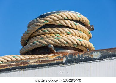Detail of mooring rope coiled around a bollard at a steel ship against a blue sky