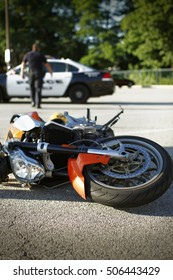 Detail of a motorcycle accident with squad car in the background.