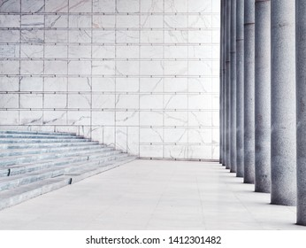 Detail of a neoclassical architectural structure with white marble walls and stone columns and a staircase
