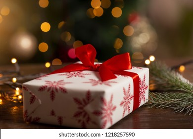 Detail of a nicely wrapped Christmas present and Christmas lights on a rustic wooden table. Selective focus