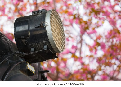 Detail of nostalgic steam locomotive headlight at pink cherry blossom background in spring (copy space)