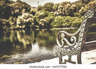 Detail of the old bench, Karavomilos lake near Sami village at Kefalonia island, Greece. Detail of the old bench, Karavomilos lake near Sami village at Kefalonia island, Greece. Vintage toned photo.