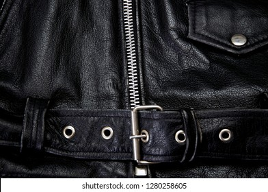 Detail of old black leather police style motorcycle jacket focusing on belt and zipper, showing flap pocket also.