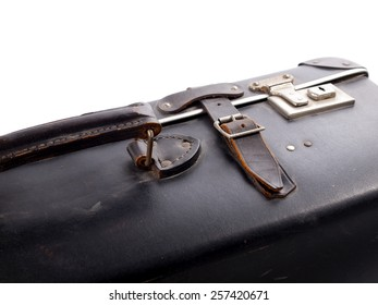 Detail of an old black vintage leather suitcase with straps and locks on a white background