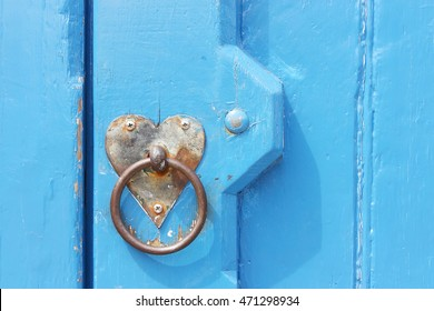 Detail of old blue door with heart formed backplate for use as a valentine card or template with copy space