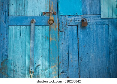 Detail of Old Blue doors with flaking paint and metal hardware in Guanajauto, Mexico