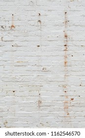 Detail of old brick wall painted white and distressed, peeling and stained. Ideal for grunge background texture