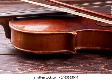 Detail of old brown violin. Vintage violin and fiddle stick close up. Equipment of classical music.