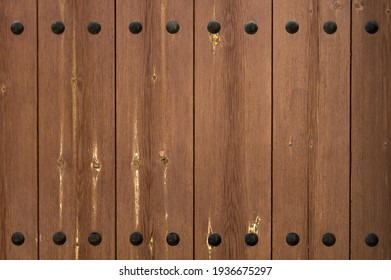 detail of an old brown wooden door with black nails