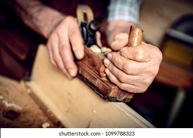 detail, old carpenter hands at work with handplaner