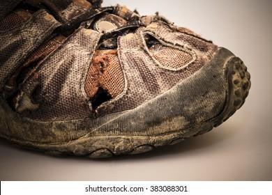 detail of old damaged hike shoe on white background