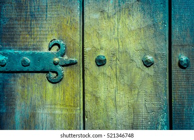 Detail of an old door handle. Rusting lock on an traditional door with paint peeling. Wooden background.