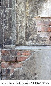 Detail of an old, gray, dilapidated facade with bricks
