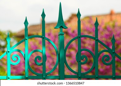 Detail of old green wrought iron gate in a park in Florence. Italy