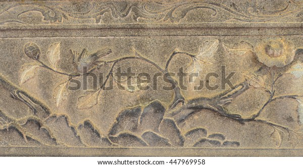 detail of a old historic carving stone relief seen at thai public temple.