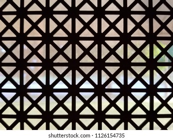 Detail of an old iron window lattice. Geometric pattern window grate. Contrast of dark and light.