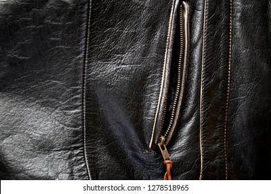 Detail of old leather motorcycle jacket focusing on unzipped side pocket