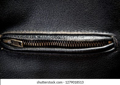 Detail of old leather motorcycle jacket focusing on brass zipper zipped closed on pocket.