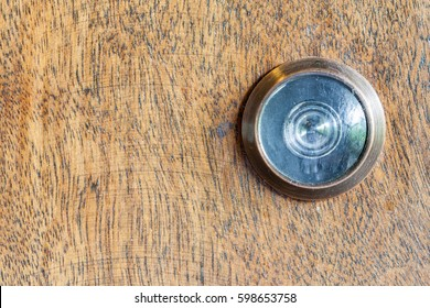 Detail of old lens peephole on wooden door background, for security in hotel.