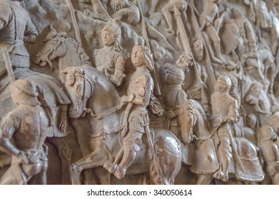 A detail of an old medieval bronze carving with knights and soldiers on the Triumphal Arch door in Naples, Italy