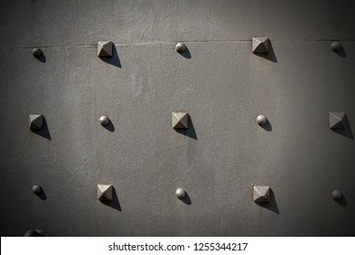 Detail of an old metal door with studs in the shape of a pyramid, background