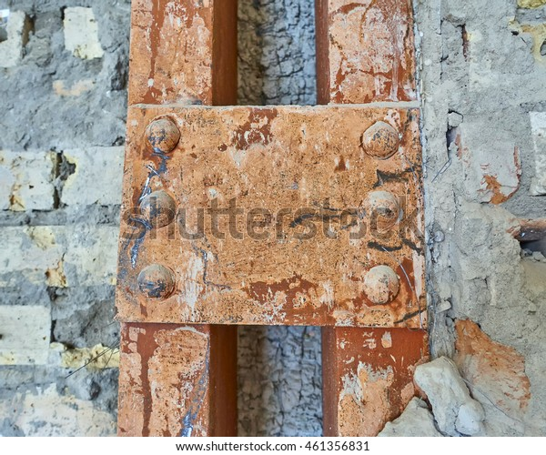 detail of old metallic supporting column in brick wall