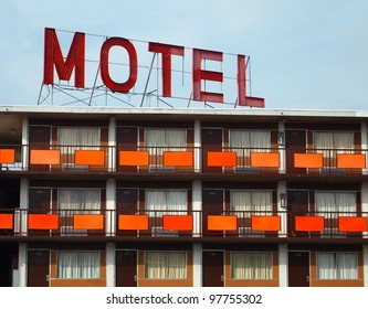 "Detail of a an old ""MOTEL"" sign atop an old motel with many rooms."