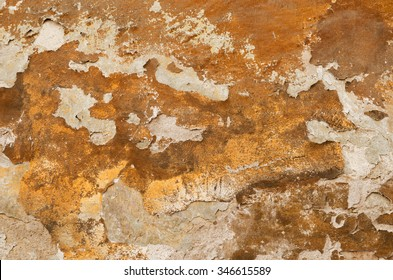 Detail of an old ocher wall with crumbling plaster