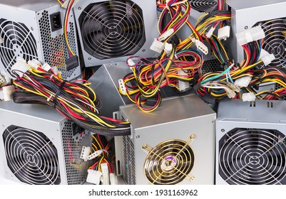 Detail of old power supply units heap as electrical background. Metal boxes stack of discarded computer hardware spare parts with fans, colorful cable bundles and white connectors. E-waste separation.