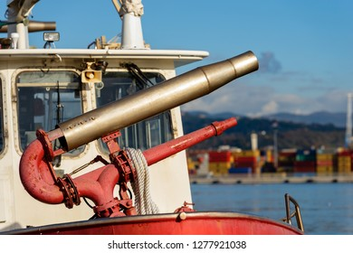 Detail of an old red water cannon aboard on a fire boat. Port of La Spezia, Liguria, Italy