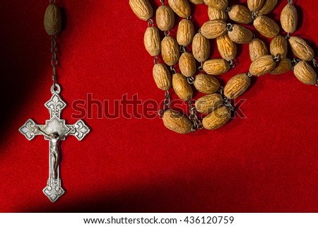 Detail of an old rosary with wooden beads and silver cross. On a red velvet background with copy space