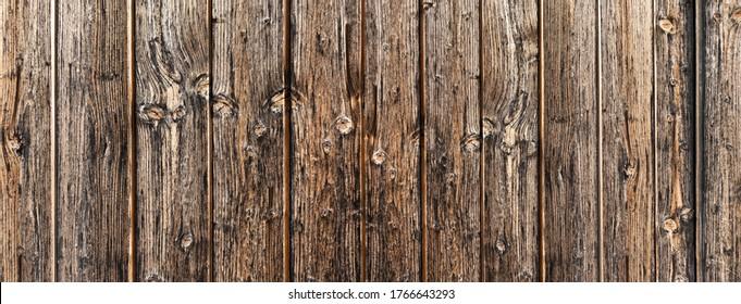 Detail einer alten rustikalen, stark verwitterten braunen Holzwand aus vertikalen Platten