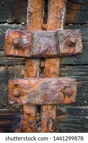 Detail of old rusting iron structure on a wooden background.
