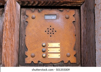 Detail of an old rusty interphone with three doorbell buttons and video camera, on a wooden door. Verona, Italy