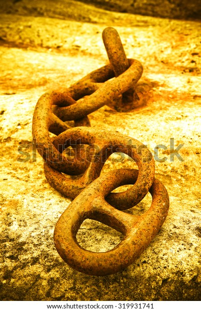Detail of an old rusty metal chain anchored to a concrete block - toned image