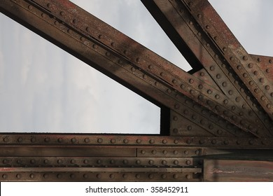 Detail of old rusty railroad bridge with rivets against the sky.