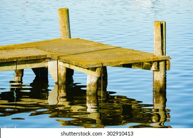 Detail of an old, unpainted wooden pier with calm and still water in background. Jetty is empty and the wood is weathered and gnarled. Poles are cracked.