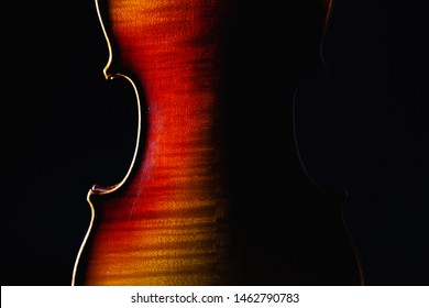 Detail of old violin music instrument of orchestra closeup isolated on black. Silhouette of a violin on black background with copy space for music concept