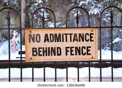 """Detail of an old, weather worn sign, posted at the Amtrak station in Staunton, VA. The sign reads """"NO ADMITTANCE BEHIND FENCE."""" Train tracks and snow can be seen in the background."""
