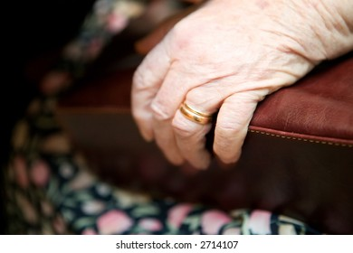A detail of an old womans hand on her purse