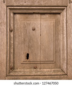 Detail of an old wooden door with rusted iron nails and with a newer keyhole suited for modern keys
