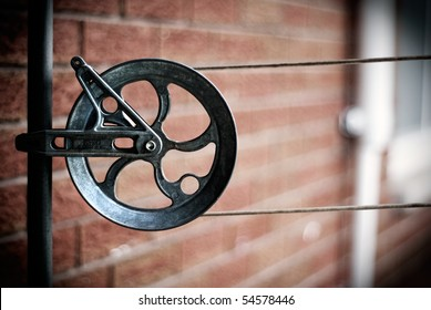 Detail of an old-style, household aluminum-alloy clothesline pulley, or wheel, on a pole. With copy-space for your text or images.