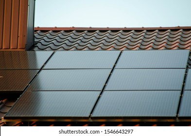 Detail on a black photovoltaic solar panels on a roof, close up photo of solar panels installation on building during sunny day, close up photo.