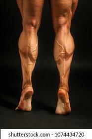 Detail on male bodybuilder calves muscles shot on black background.