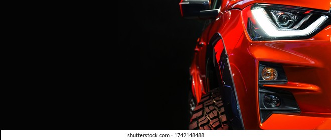 Detail on one of the LED headlights red Pickup Truck on black background,copy space